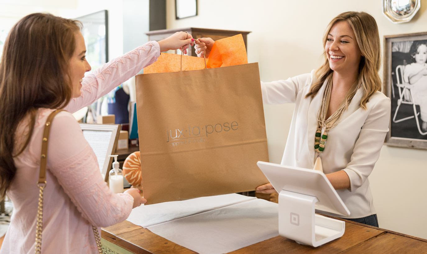 A woman customer being handed a shopping bag at the counter